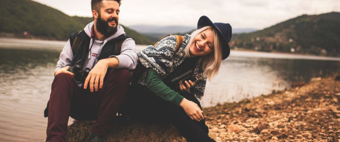 Young smiling couple enjoying nature and their hiking together